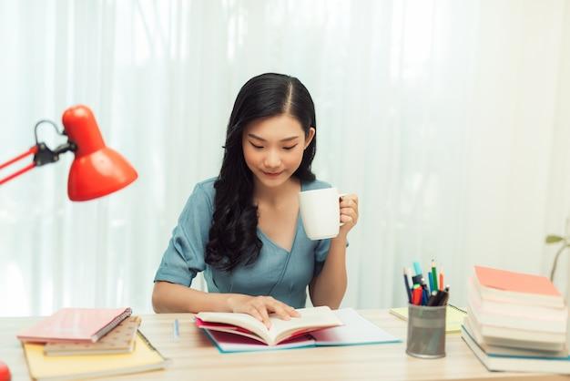 Tempo livre. jovem de óculos lendo um livro sentada em casa, bebendo chá,