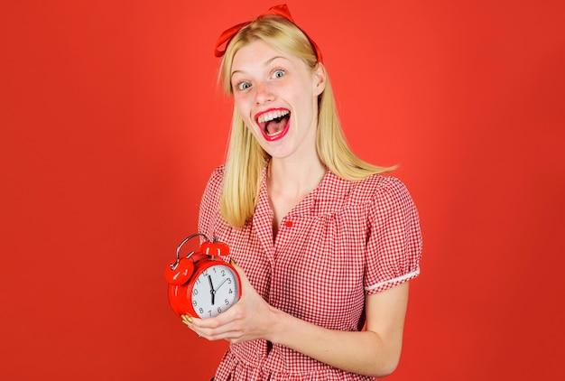 Tempo, mulher sorridente com despertador, linda garota com despertador retrô, economizando o conceito de tempo.