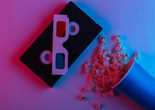 Tempo ovie balde de papelão com cassete de vídeo pipoca e óculos 3d descartáveis de papel anáglifo estereoscópico em luz de néon gradiente azul rosa vista superior