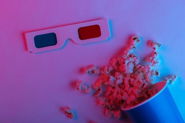Tempo ovie balde de papelão com pipoca e óculos 3d descartáveis de papel anáglifo estereoscópico em luz de néon gradiente azul rosa vista superior