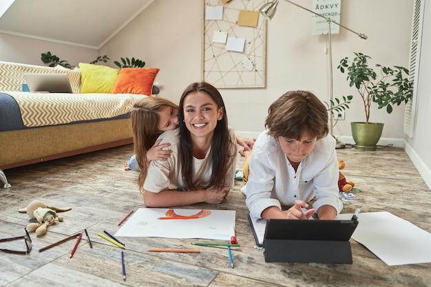 Tempo para a família adolescente deitado no chão da sala de estar usando tablet digital e fazendo lição de casa