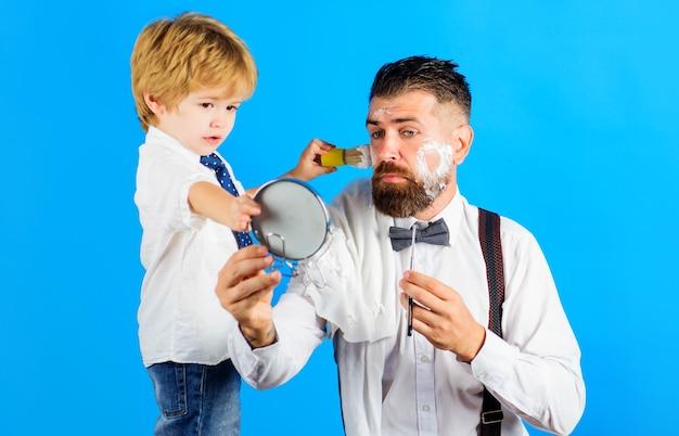 Tempo para a família. dia dos pais. filho e pai barbeando a barba. assistente para o pai. pequeno barbeiro. barbearia.