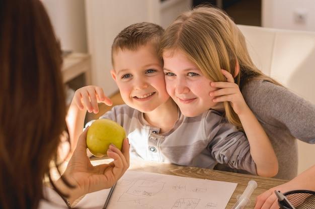 Tempo para a família em casa. mãe, dar, maçã, para, crianças