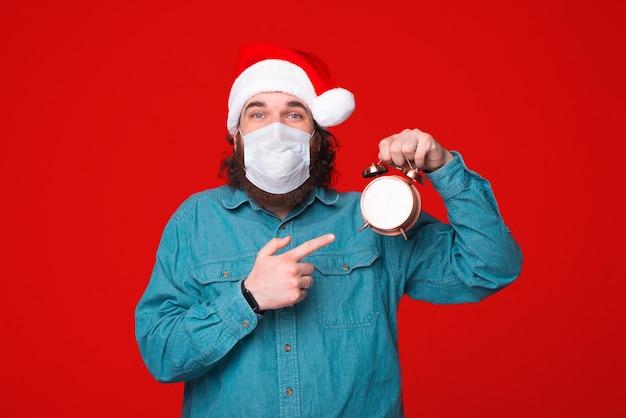 Tempo para férias e proteção, homem barbudo com chapéu de papai noel e máscara de proteção apontando para o relógio