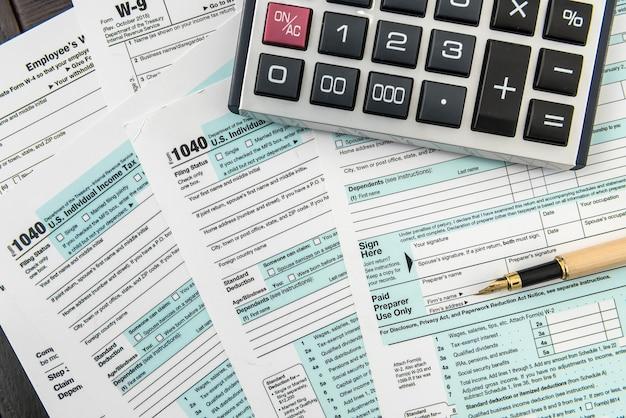 Tempo para impostos, formulário federal com caneta e calculadora, mesa de escritório