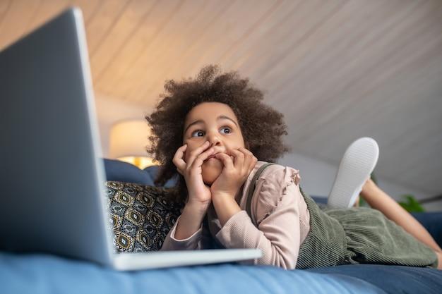 Tempo para pensar. menina afro-americana bonitinha, pensativa, olhando para o lado, deitada no sofá em casa na frente do laptop