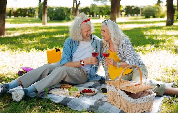 Tempo prazeroso. casal simpático encantado bebendo vinho enquanto faz um piquenique romântico
