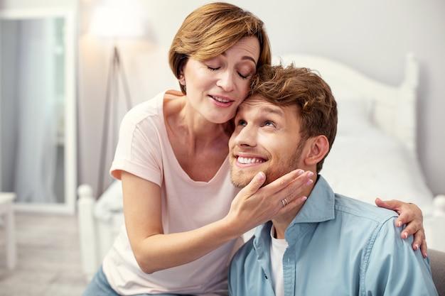 Tempo prazeroso. mulher agradável e simpática fechando os olhos enquanto aproveita o tempo com seu filho