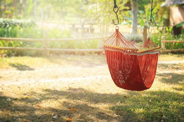 Tempo preguiçoso com a rede no jardim do verão, vintage tonificado.