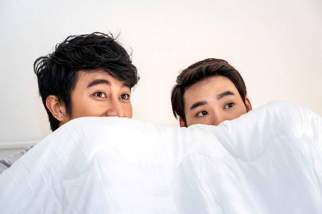 Tempo romântico. casal homossexual asiático de pijama brincando de esconde-esconde na cama. conceito lgbt gay.