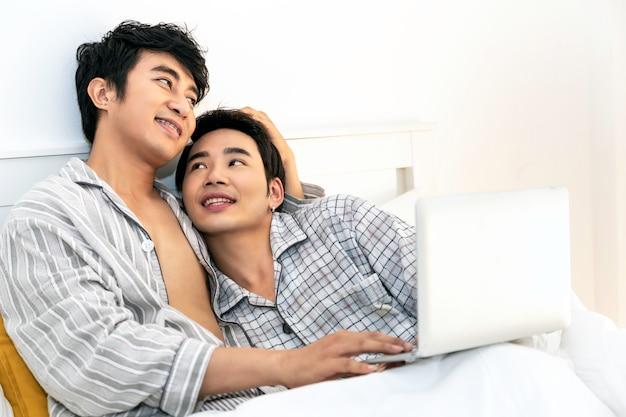 Tempo romântico. casal homossexual asiático de pijama, compras on-line com o notebook computador na cama. conceito lgbt gay.