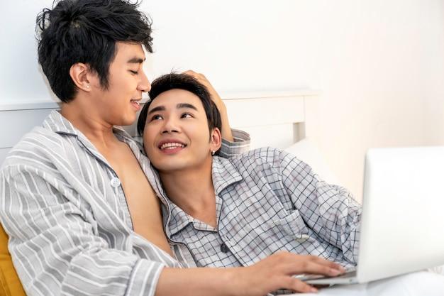 Tempo romântico. casal homossexual asiático de pijama, compras on-line com o notebook computador na cama