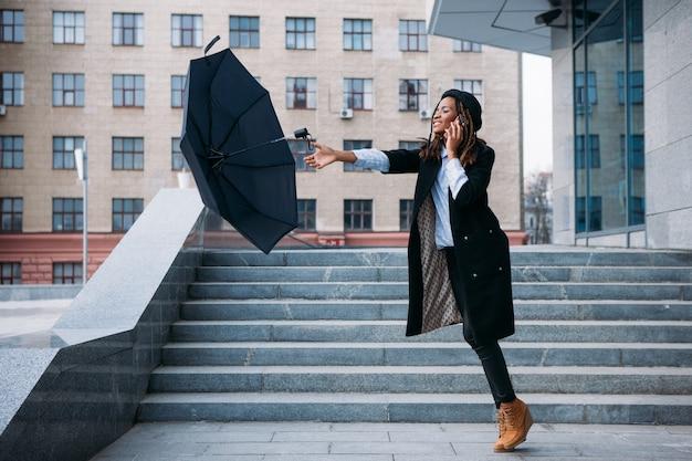 Tempo tempestuoso. garota negra pegando guarda-chuva voador enquanto fala no celular na rua, conceito de leveza