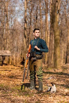 Temporada de caça do outono. caçador de homem com uma arma whit seu cão. caça na mata