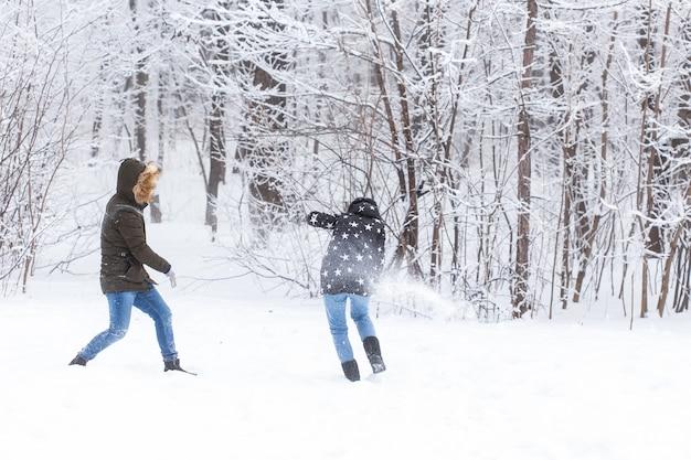 Temporada de diversão e conceito de lazer casal apaixonado jogando madeira de inverno na neve