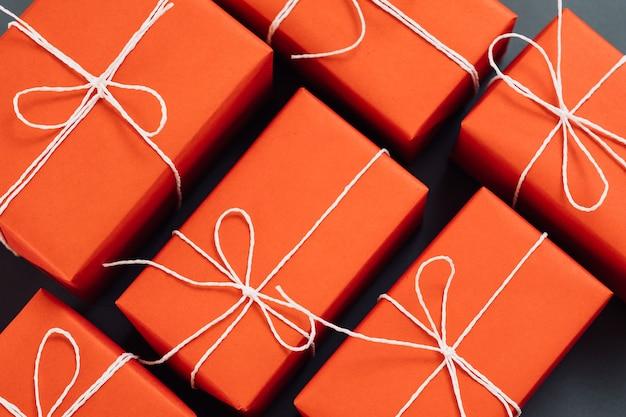Temporada de férias e parede de natal. apresenta-se em embalagem de papel vermelho amarrada com pano de fundo de barbante branco.