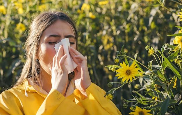 Temporada de gripe resfriada, nariz escorrendo. árvores floridas no fundo. menina espirrando e segurando papel