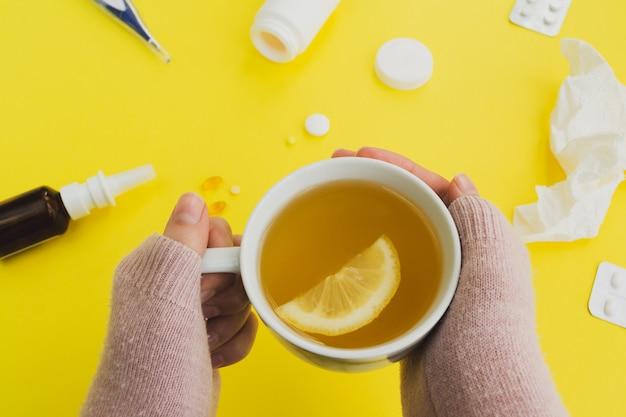 Temporada de gripes e resfriados. mulher com uma caneca de chá e comprimidos