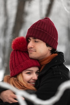 Temporada de inverno nevado com casal abraçando