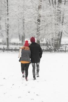 Temporada de inverno nevado com casal na parte de trás
