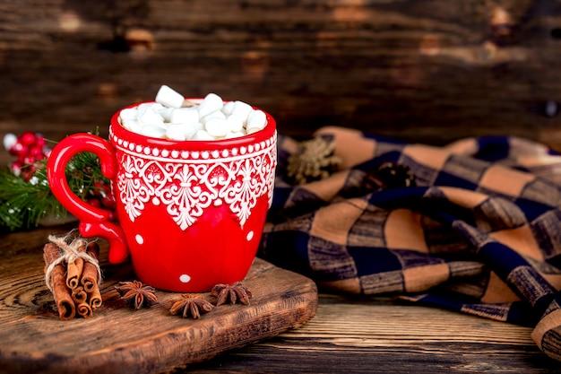 Temporada de inverno sup com cacau e marshmallows com manta aconchegante na mesa de madeira