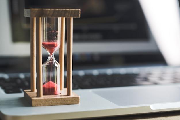 Temporizador de relógio de areia no laptop .symbol do tempo