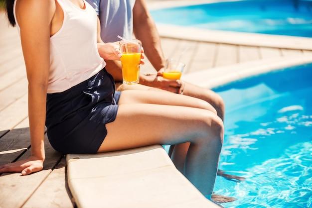Tempos de lazer à beira da piscina. close de um casal em trajes casuais sentados à beira da piscina e bebendo coquetéis