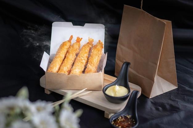 Tempura de camarão em embalagem de papel, fundo escuro com fumaça.