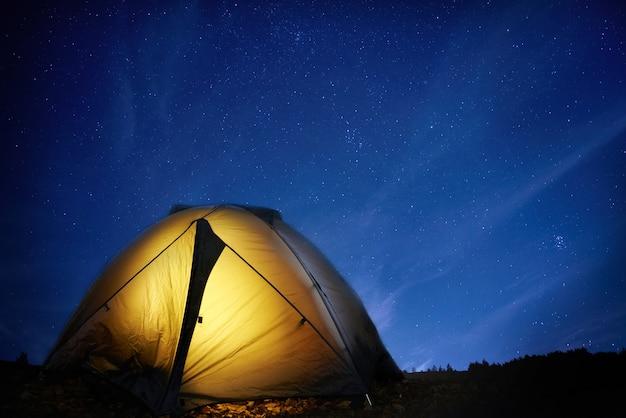 Tenda de acampamento amarela iluminada sob as estrelas à noite