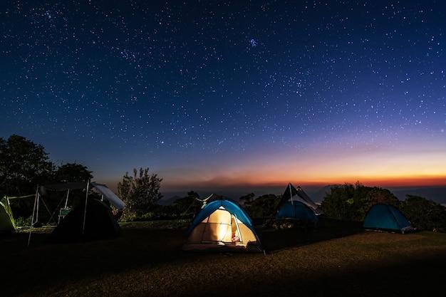 Tenda de acampamento brilhante na montanha sob um lindo céu estrelado à noite, estilo de vida de viagem
