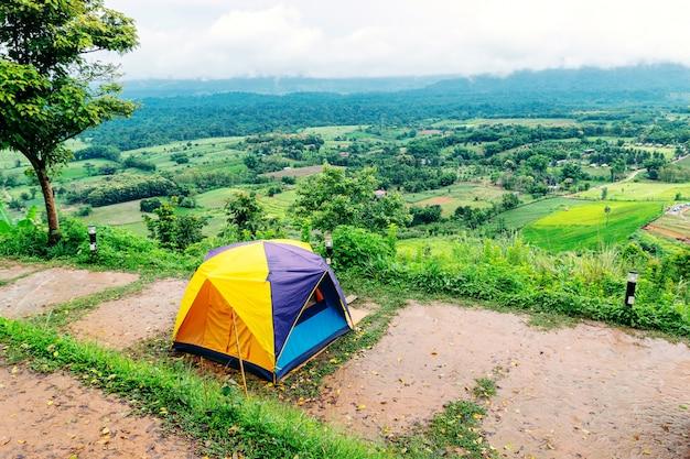 Tenda de acampamento montada no ponto mais alto de uma alta montanha com céu e montanhas ao fundo.