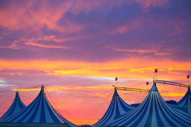 Tenda de circo em um dramático céu do sol colorido