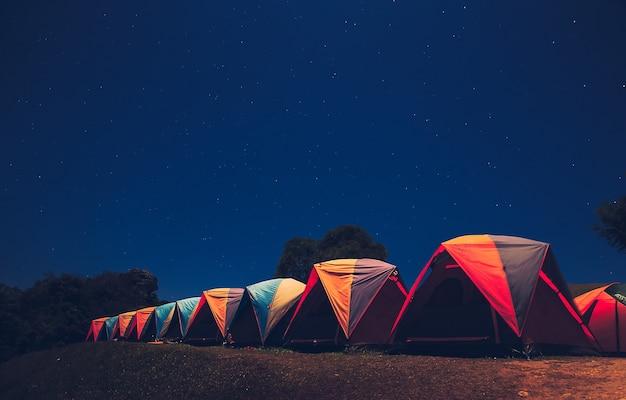 Tenda de incandescência nas montanhas sob um céu estrelado