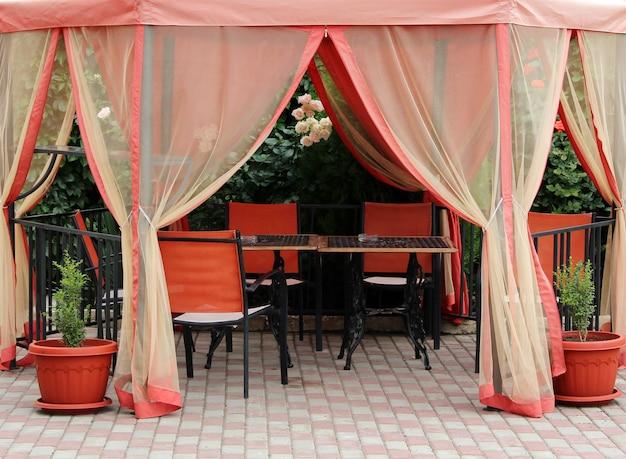 Tenda de verão do sol e mesas para relaxar ao ar livre
