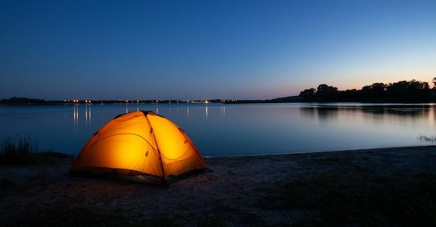Tenda laranja iluminada em um lago ao entardecer