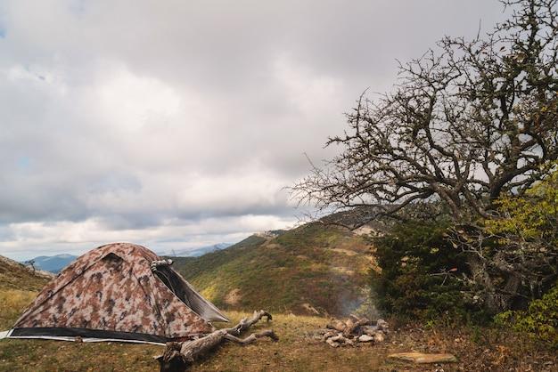 Tenda nas montanhas perto de uma fogueira em uma caminhada em um acampamento turístico, atividade, descanso, relaxamento, silêncio