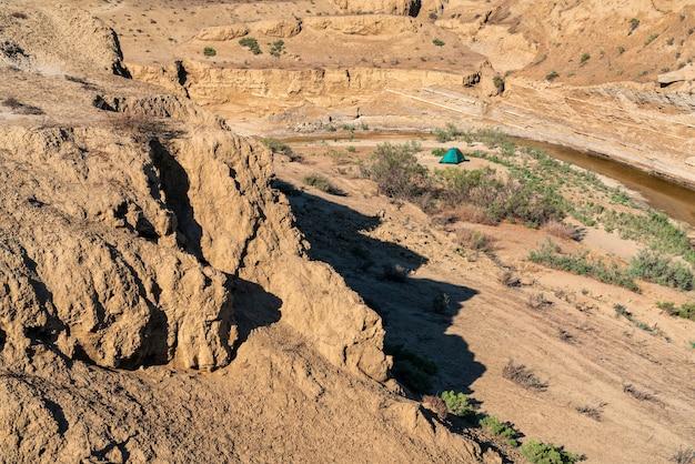 Tenda para turistas em uma área montanhosa e deserta perto de um pequeno rio