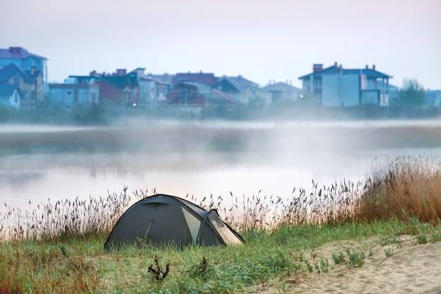 Tenda verde perto do rio com névoa matinal na água. paisagem de viagens ao ar livre