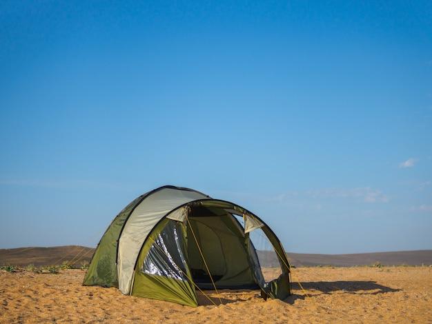 Tenda verde solitária na costa, contra o céu azul com nuvens de luz