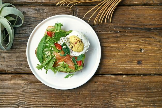 Tendência comida de rua - torrada de abacate com guacamole, ovo escalfado e salmão em um prato em um de madeira