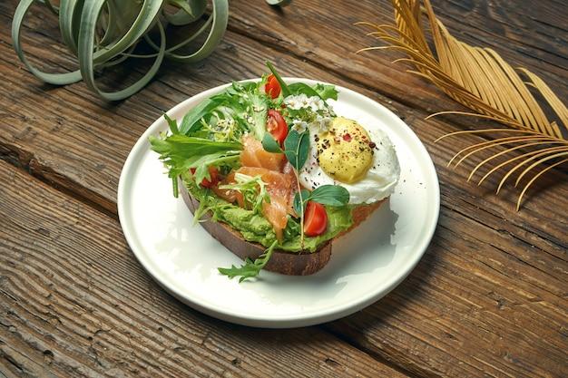 Tendência comida de rua - torrada de abacate com guacamole, ovo escalfado e salmão em um prato sobre uma mesa de madeira