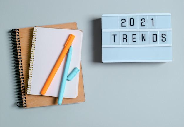Tendência conceito 2021, caixa de luz com inscrição, registros de caderno, canetas, flor.