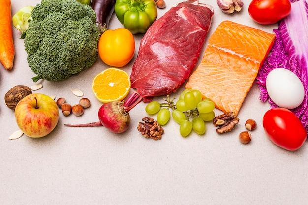 Tendência da dieta paleo / pegan. conceito de comida equilibrada saudável. conjunto de produtos frescos, carne crua, salmão, legumes e frutas