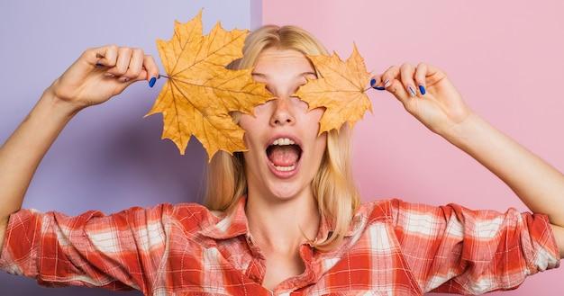 Tendência da moda outono. garota surpresa com folhas de plátano. mulher bonita com folha de ouro. humor outonal.