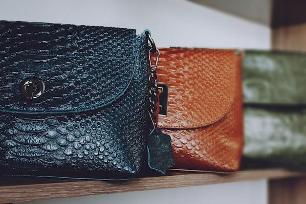 Tendência da moda python pele de cobra imprima bolsas na prateleira de uma loja, loja.