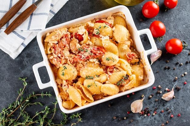 Tendências da receita viral de tomate assado e queijo feta com macarrão. fetapasta sobre um fundo escuro. copie o espaço. vista do topo.