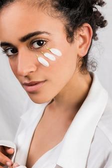 Tender mulher étnica com pétalas brancas no rosto