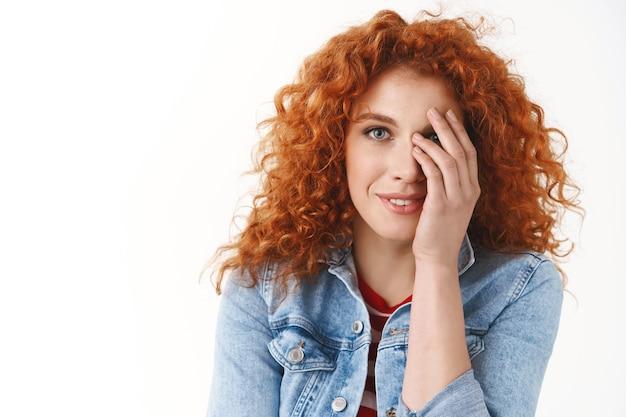 Tender sensual feminino ruivo europeu mulher fechar metade rosto olhar gentil feliz câmera sorrindo bobo glamour olhar divertidamente escondendo o olho em pé parede branca relaxado e coquete
