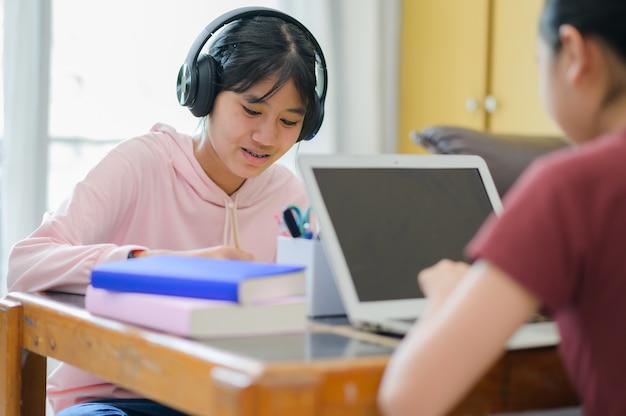 Tendo aula online. crianças asiáticas estudam sozinhas com e-learning em casa. educação online, auto-estudo e conceito de educação escolar em casa.