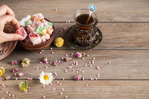 Tendo doces lokum com um copo de chá